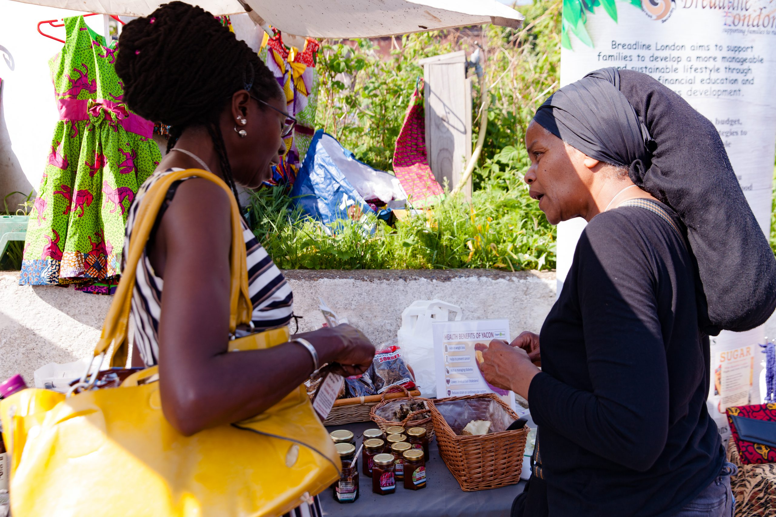 Two black women stand in front of a market stall for the social enterprise Breadline London - which aims to support families to raise themselves out of the cycle of poverty through financial education, training, practical workshops, and business opportunities.